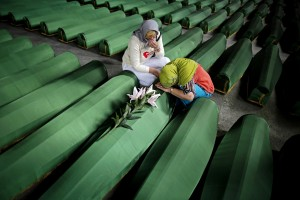 Bosnian Muslim women cry near the coffin of their relative, which is one of the 175 coffins of newly identified victims from the 1995 Srebrenica massacre, in Potocari Memorial Center, near Srebrenica, July 10, 2014. Family members, foreign dignitaries and guests are expected to attend a ceremony in Srebrenica on July 11, marking the 19th anniversary of the massacre in which Bosnian Serb forces commanded by Ratko Mladic killed up to 8,000 Muslim men and boys. The remains of 175 identified victims will be buried at a memorial cemetery during the ceremony. Their bodies were found in some 60 mass graves around the town. REUTERS/Dado Ruvic (BOSNIA AND HERZEGOVINA - Tags: POLITICS ANNIVERSARY SOCIETY CONFLICT OBITUARY)